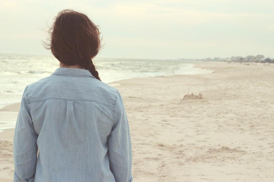 Frau geht allein am strand entlang