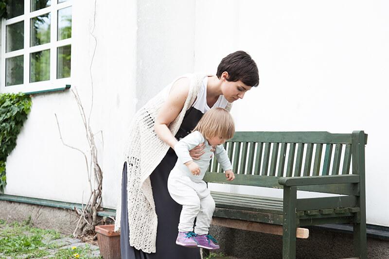 konsequenz in der Kindererziehung mama mit Tochter vor einem alten haus auf einer bank