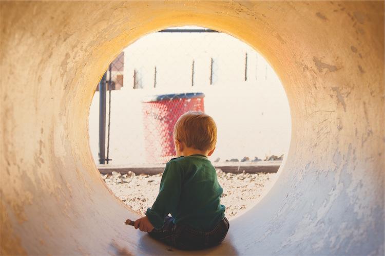 kind spielt in einem rohr am parkplatz