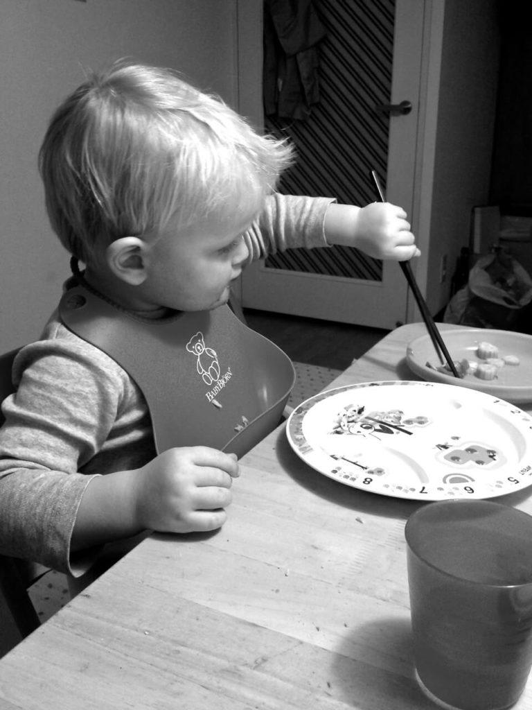 kleiner bub isst mit japanischen stäbchen