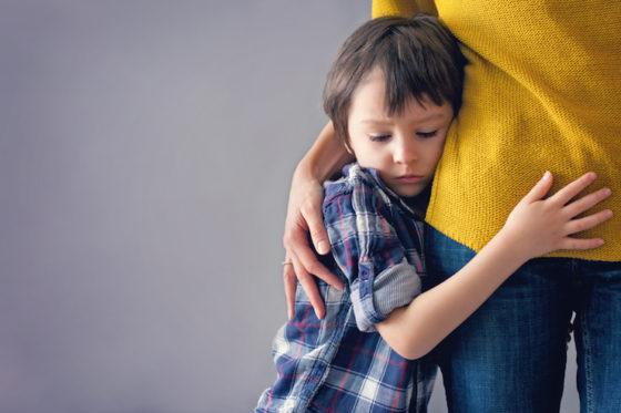 trauriges kind umarmt seine mama